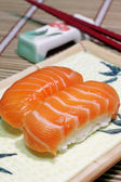 Yummy salmon. A close-up of chopsticks and a square plate with t — Stock Photo