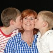 Mother and her two sons kissing — Stock Photo