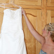 Bride putting on her wedding dress - Stock Photo