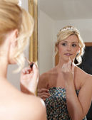 Bride putting on her makeup in the mirror — Stock Photo