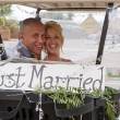 Bride and Groom in a Golf Cart - Stock Photo