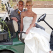 Bride and Groom in a Golf Cart — Stock Photo #6284915