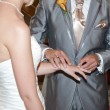 Bride and Groom in church exchaning rings - Stock Photo