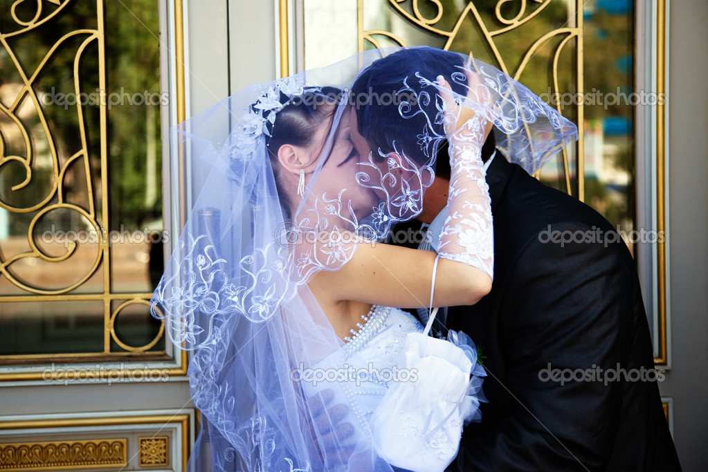 Close up of a bride's hand holding her veil while the couple kisses. — Stock Photo #6119846