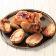 Roast chicken and potatoes - Stock Photo