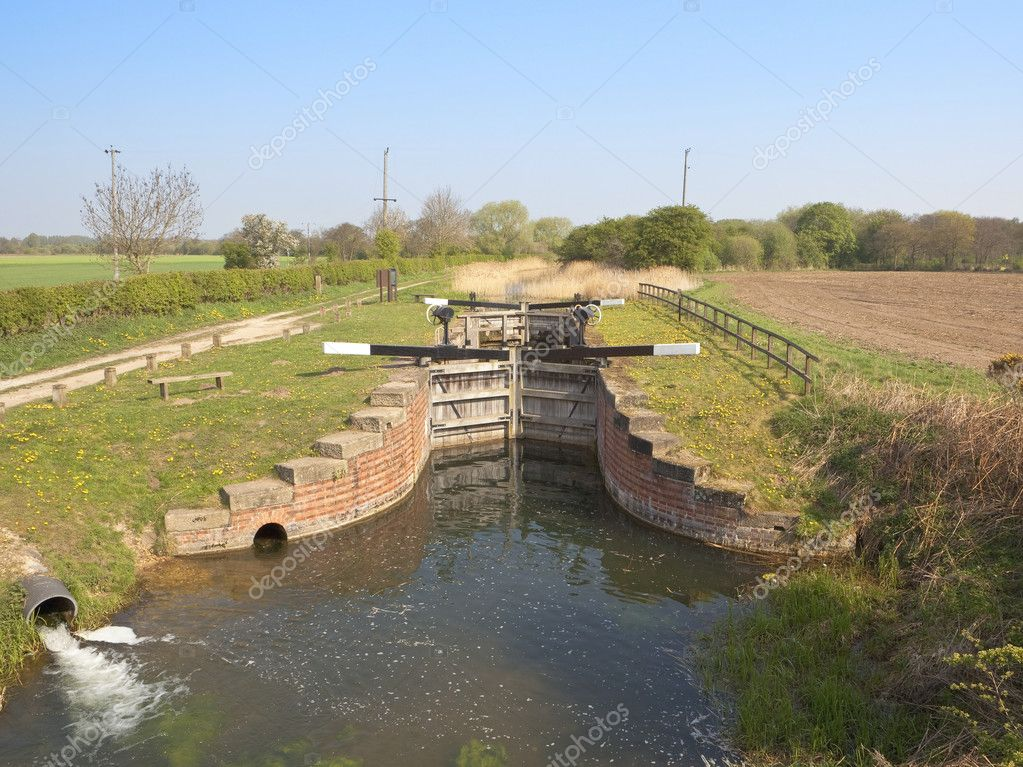 An english landscape with a waterway and lock gates beside a towpath under a blue sky in springtime  Stock Photo #5459855