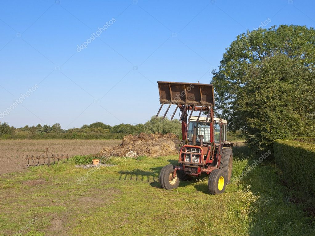 A small red tractor with loading bucket attached parked by a manure heap at the edge of a field under a clear blue sky — Stock Photo #6016062