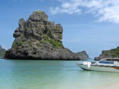 Photo a tropical landscape boat on the sea and a rock — Stock Photo