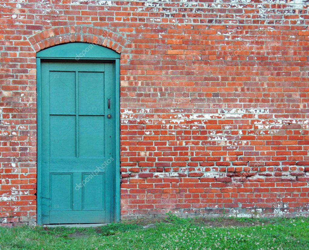 Very rustic green door set in an old brick wall. — Photo #6125706