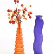 Still life of a branch with small apples in colored glass vase — Stock Photo