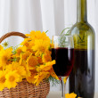 A bottle of rose wine with a glass and yellow flowers in a baske — Stock Photo #6015350