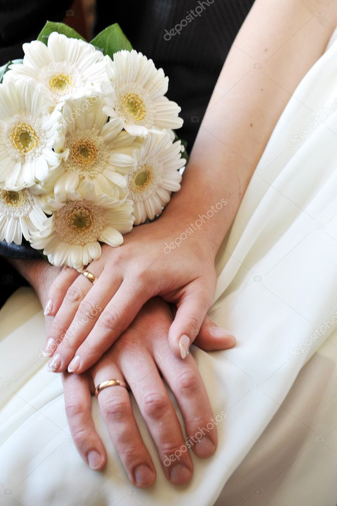 2 hands with wedding rings and flowers