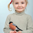 Little girl and bullfinch — Stock Photo #5868851