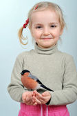 Little girl and bullfinch — Stock Photo