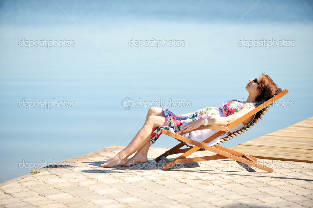 Woman sitting in  lounge chair. summer's day on lakeside — Stock Photo #6362181