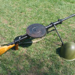 Machine gun and military helmet on green grass — Stock Photo #5591958