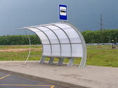Bus stop with pavilion on asphalt road — Stock Photo
