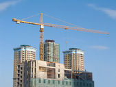 Yellow hoisting crane and some constructing buildings — Stock Photo