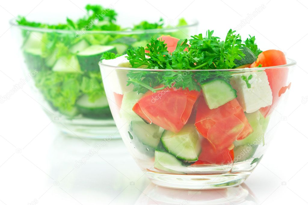 Two various salads of assorted vegetables in glass bowls isolated on white background.  Stock Photo #5601357