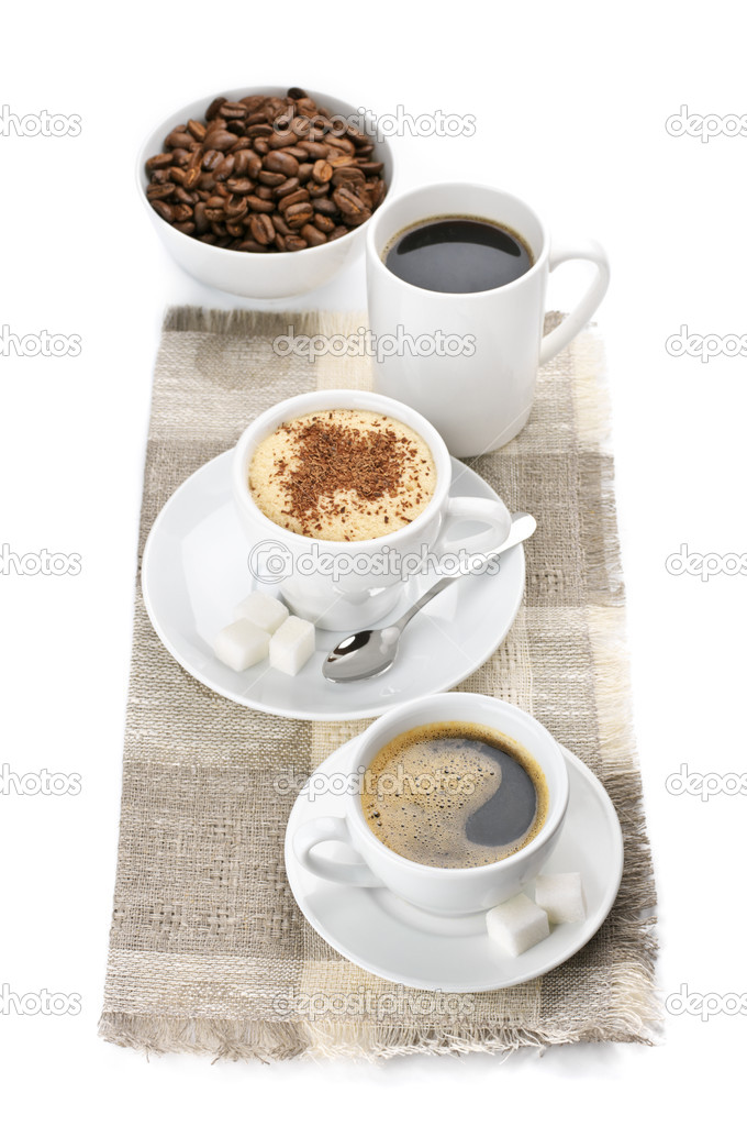 Three white cups and bowl of assorted coffee on linen napkin isolated against white background. — Stock Photo #6404320