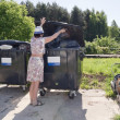 The rural woman throws out household garbage — Stock Photo