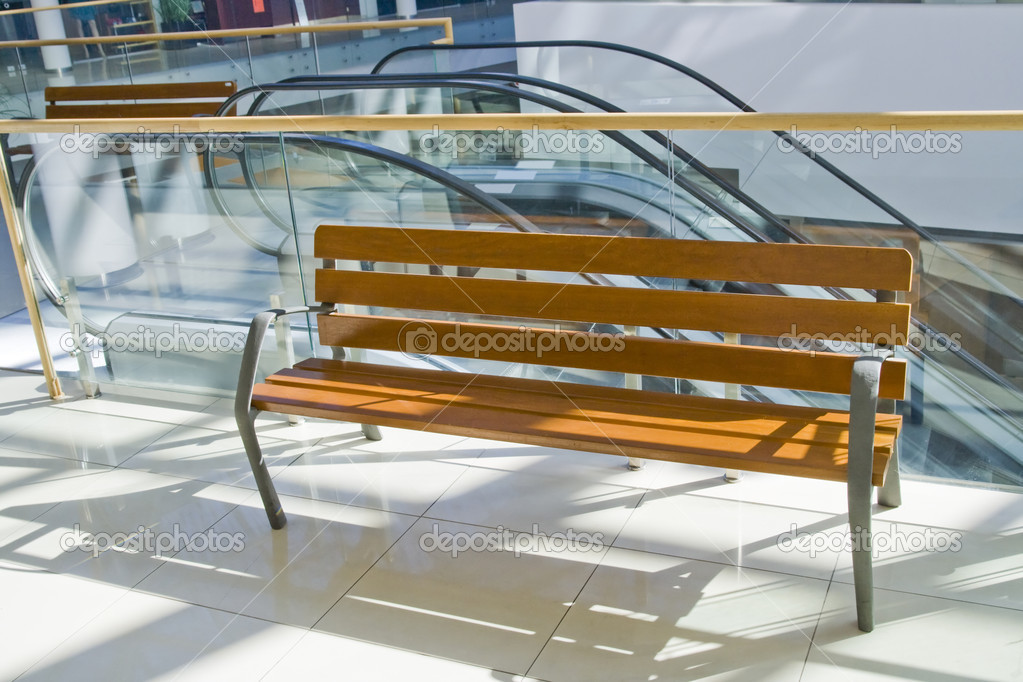 The wooden bench  in a hall of a modern building, it is shined by the sun  Stock Photo #6366915