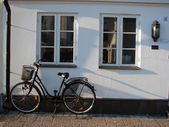 White wall with windows and bicycle — Stock Photo