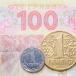图库照片: One kopek and hrivncoins against one hundred bill