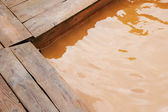 Wooden platform and thermal water in hot pond — Stock Photo
