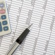 Stockfoto: Calculator and Pen on Spreadsheet