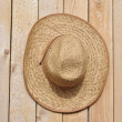 Straw hat on a wooden wall - Stock Photo