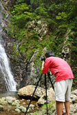 Photographer taking picture of waterfall — Stockfoto