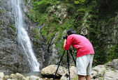 Photographer taking picture of waterfall — Stock Photo