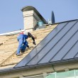 The roofer behind work on repair a roof - Stock Photo