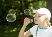 Girl and multi-colored soap bubbles — Stock Photo