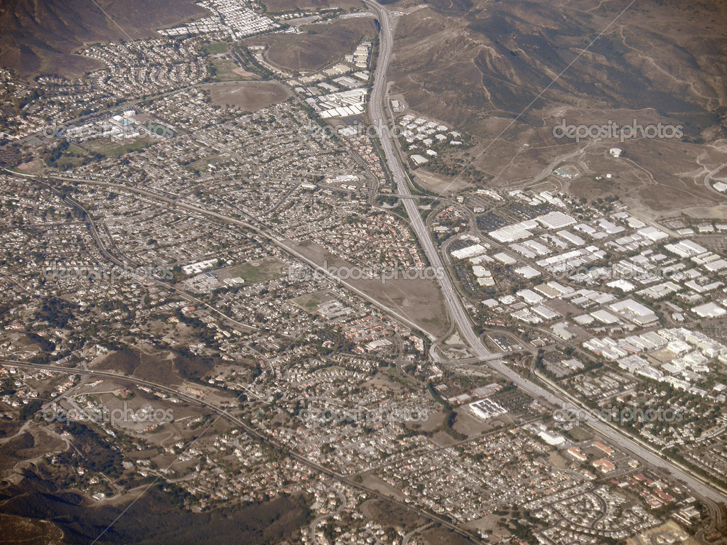 Highway stretches through LA Suburbs and Mountains with roads exited into the landscape.  Aerial Photograph. — Stock Photo #5762427