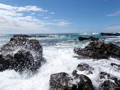 Wave crashes along lava rocks and sprays water into the air on r — Stock Photo