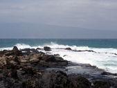 Dimma från vågor sprayer i luften som det kraschar mot lava roc — Stockfoto