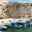 Gallipoli, Apulia - Angevin castle with fishing boats - Stock Photo