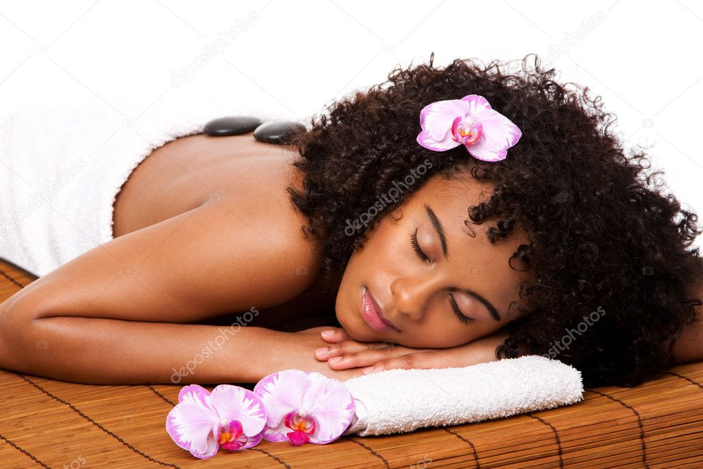 Beautiful happy relaxed Latina-African woman at health day spa with hot stone massage treatment laying in white towel on bamboo table decorated with orchids. — Stock Photo #5634018