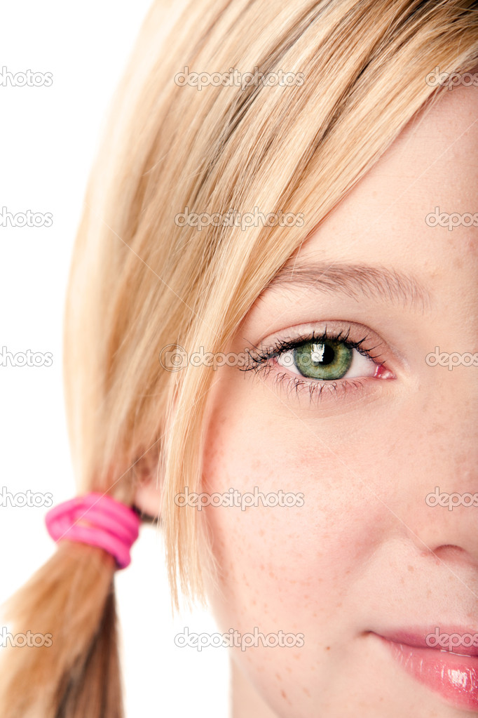 Beautiful green watchful eye of a teenage girl with blond hair pigtail, ...