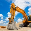 Foto Stock: Yellow Excavator at Construction Site