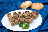 Grilled meat balls and rissole arranged with loafs of brad — Stock Photo