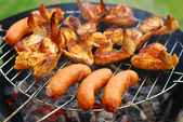 Sausages and chicken wings on the grill — Stock Photo