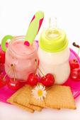 Cherry yogurt and bottle of milk for baby — Stock Photo