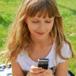 Young girl sending sms by mobile phone — Stock Photo #6021260