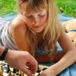 Stock Photo: Young girl playing chess outside