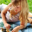 Young girl playing chess outside — Stock Photo