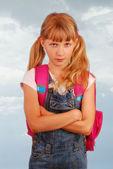 Angry schoolgirl against cloudy sky — Stock Photo