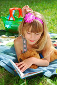Young girl reading a book on the picnic — Stock Photo